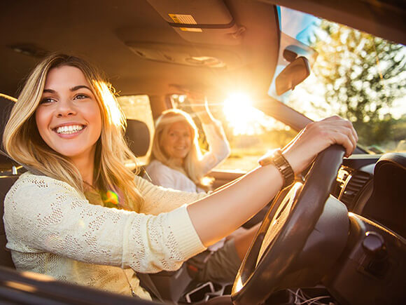 young female driver with mother in car smiling looking out of driver side window
