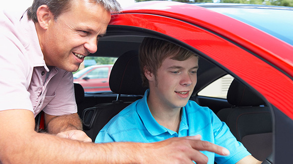 teenage boy learning to driver with instructor showing car controls
