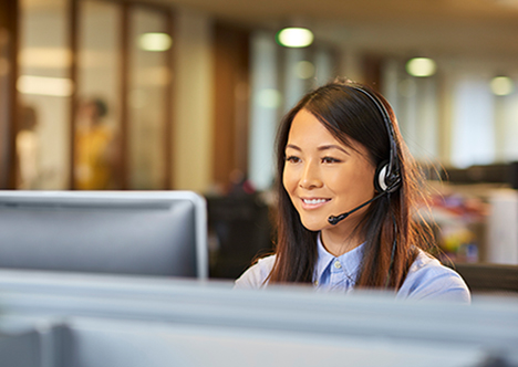 young happy lady working in call centre on headset